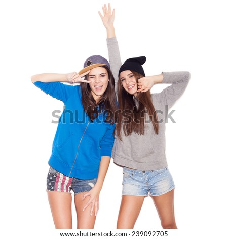 Two young stylish girlfriends in hoodies having fun together.  indoor portrait. White background not isolated - stock photo