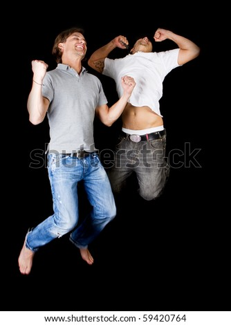 Two young successful jumping in joy! Two handsome multiracial models. - stock photo