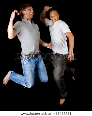Two young successfull men jumping in joy. Fresh multiracial models. - stock photo