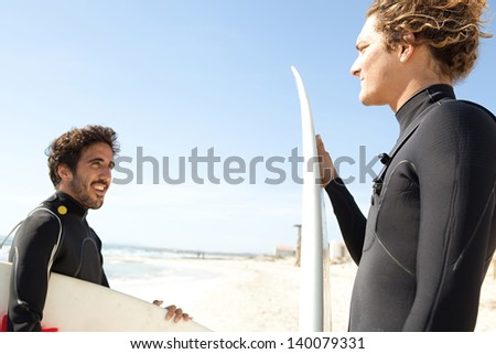 Two young surfers sports men wearing surfing neoprene waterproof suits and carrying their surfing boards on a white sand beach with a blue sky in the background during a sunny day. - stock photo