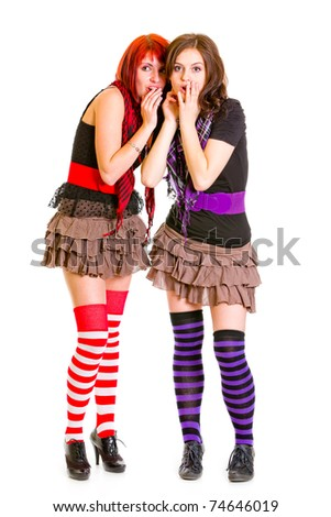 Two young surprised girlfriends standing together and holding hands near mouths isolated on white - stock photo