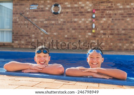 Two young swimmers happy in their private inground pool - stock photo