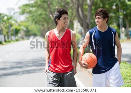 Two young talking basketball players walking in the park