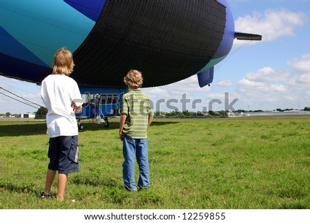 Two young teenage boys studying an airship as it swings o nits tether. - stock photo