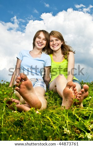 Two young teenage girl friends sitting barefoot on summer meadow