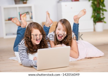 Two young teenage girls laying on the bedroom floor over pillows and using a laptop, laughing out loud - stock photo