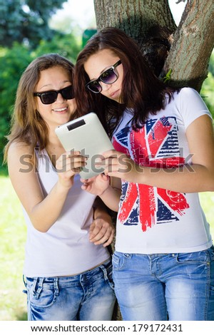 Two young teenage girs studens sitting in park with tablet pc - stock photo