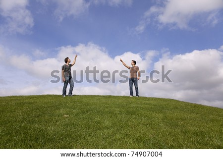 two young teenager in the park pointing to the sky