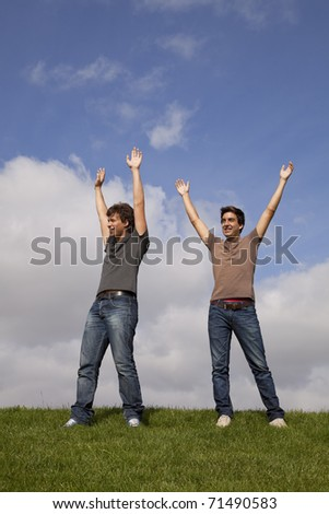 two young teenager with the arms outstretched in outdoor - stock photo