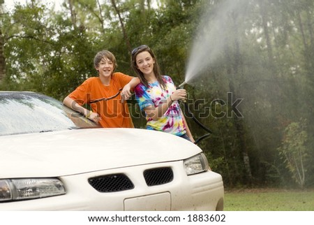 two young teens - boy and a girl - at home washing the car - stock photo