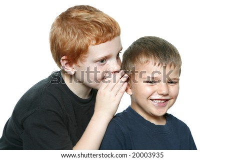 Two young toddler boys telling a secret; one boy is laughing.