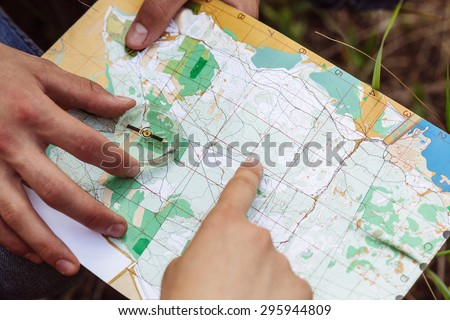 two young tourist determine the route map and compass - stock photo