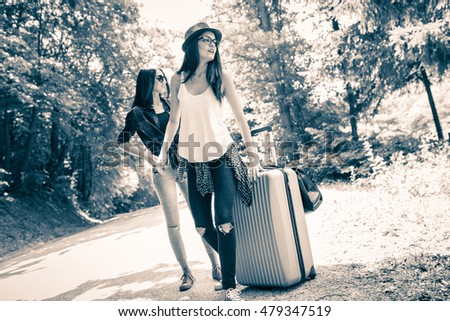 Two Young Tourist Girl Hitchhiking On The Road