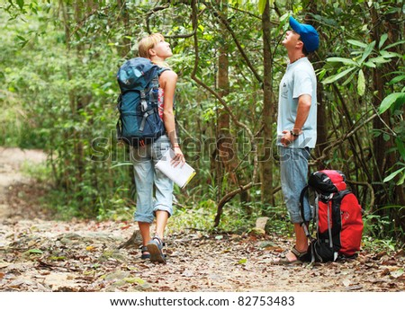 Two young tourist people with the map looking to the upward in the forest - stock photo