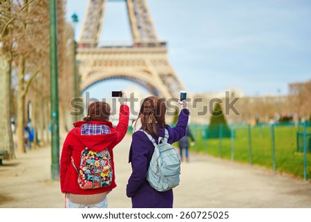 Two young tourists in Paris taking picture of the Eiffel tower - stock photo