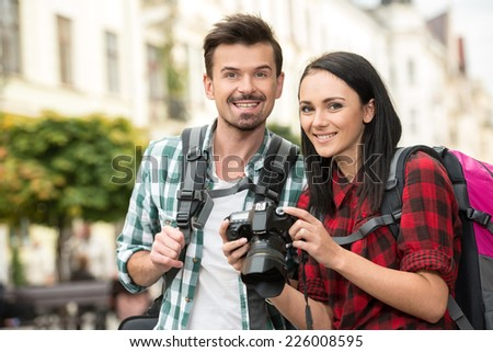 Two young tourists with backpacks and camera. Sightseeing City. - stock photo