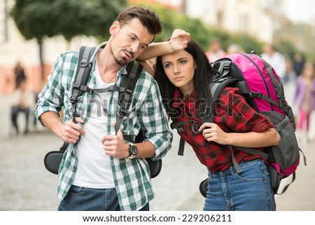 Two young tourists with backpacks are sightseeing city. Tired. - stock photo