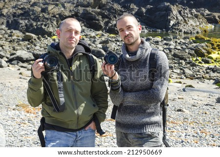 Two Young Tourists With Backpacks Sightseeing and making photos on nature