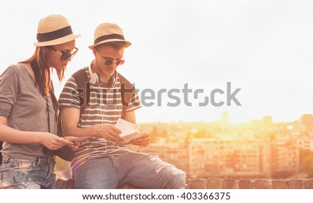 Two young tourists with souvenirs - Sunset, Golden hour, City View, Traveling - stock photo