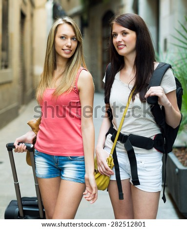 Two young travelers with baggage heading to hotel on foot