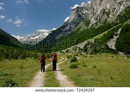 Two young trekkers walking along a mountain path, Ropojana Valley, Montenegro - stock photo