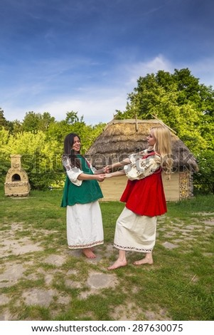 Two young ukrainian women in national costumes at the vilage yard  - stock photo