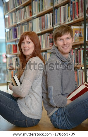 Two young university students sitting back to back in a library and ?miling at camera