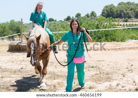 Two young veterinary mounted on horseback at the farm
