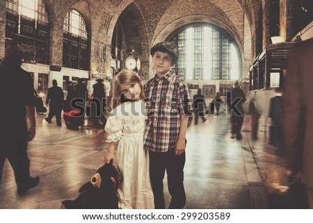 Two young vintage travel children are standing in an old train station waiting for transportation for an imagination or journey concept. - stock photo