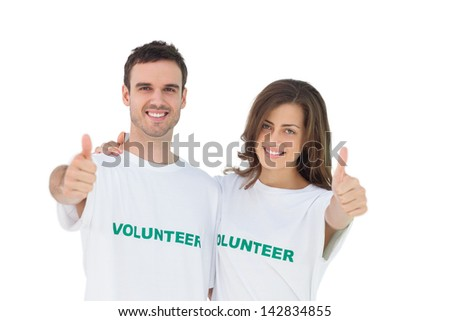 Two young volunteers giving thumbs up on white background - stock photo