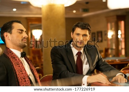 Two young well-dressed men behind gambling table in a casino