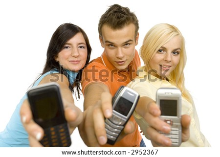 Two young woman and a man between them. They're showing mobile phones' screen. Isolated on white in studio. - stock photo