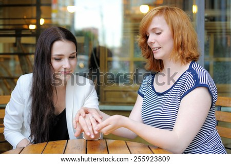 Two young woman at the outdoors cafe
