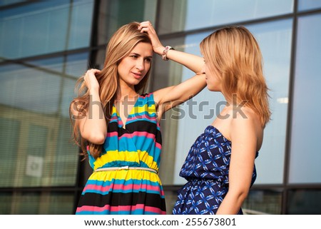Two young woman chatting outdoors - stock photo