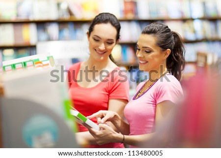 two young woman choosing a book in bookstore or library - stock photo