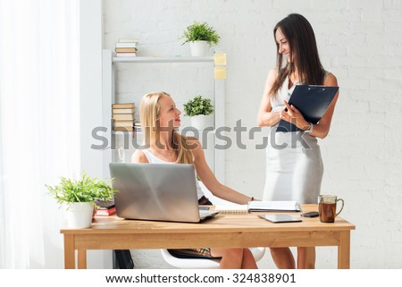 Two young woman colleague at office working standing and talking. - stock photo
