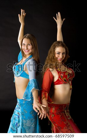 Two young woman dance and smile