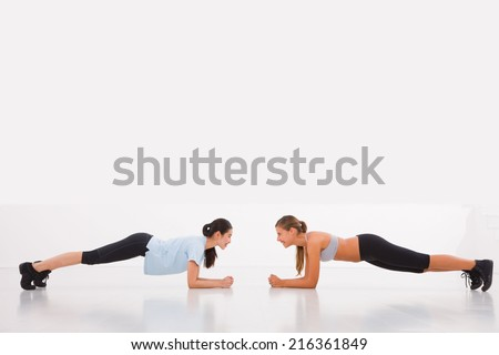 Two young woman doing push-ups in gym - stock photo