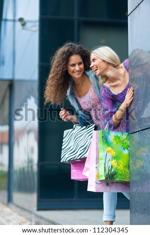 two young woman friends with shopping bags smiling and having fun - stock photo