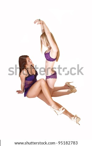 Two young woman in lingerie playing in there studio, one sitting, one  kneeling in heels for white background. - stock photo