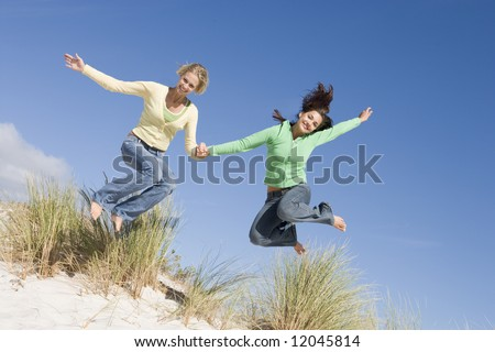 Two young woman in mid-air leap at beach - stock photo