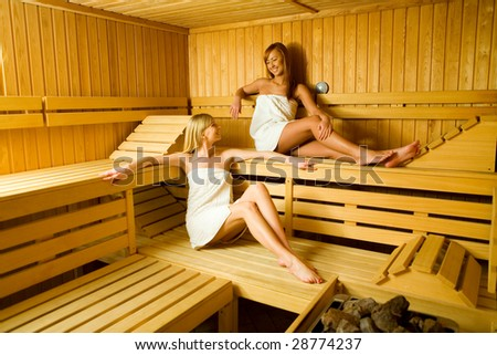 Two young woman in sauna. They looks happy. - stock photo