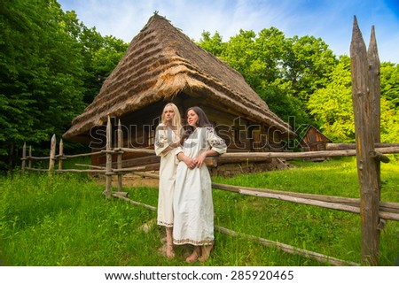 Two young woman in ukrainian national costumes near old wooden house (wide angle lense) - stock photo