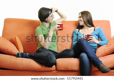 two young woman isolated on white with cup off coffee talking and chating isolated on white on orange sofa