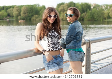 Two young woman relaxing near the water. Outdoors, lifestyle
