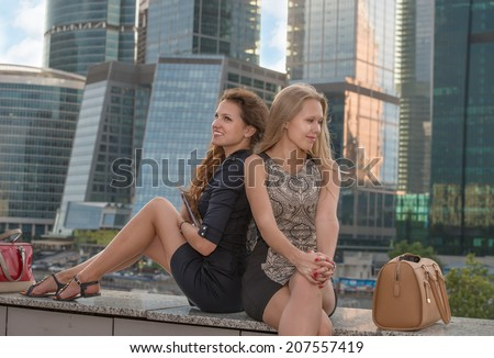 Two young woman resting near skyscrapers