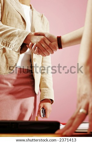 two young woman shake hands in work environment - stock photo