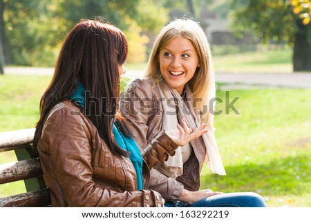 Two young woman sitting in the park and talking about something,Friends talking - stock photo