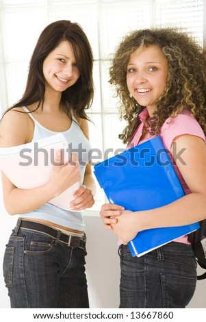 Two young woman standing near window and holding notebooks. Looking at camera. - stock photo