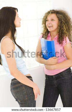 Two young woman standing near window and talking. One of them holding notebook. Side view. - stock photo